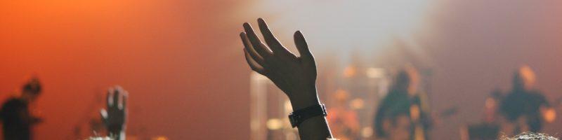 people raising hands during worship